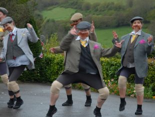 A group of five dancers dressed in fake ginger moustaches, tweed jackets, caps and waistcoats, pose on a road in a scenic landscape.