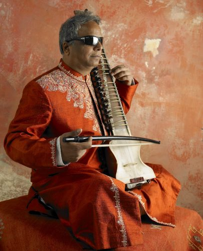 Wearing traditional Indian red robes, Baluji Shrivastrav poses, facing the camera side-on