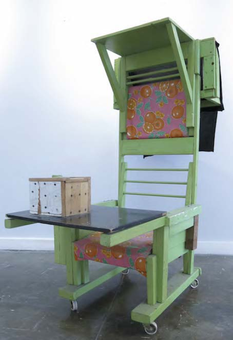 A large wooden green chair stands on wheels with a table attached at the front of it