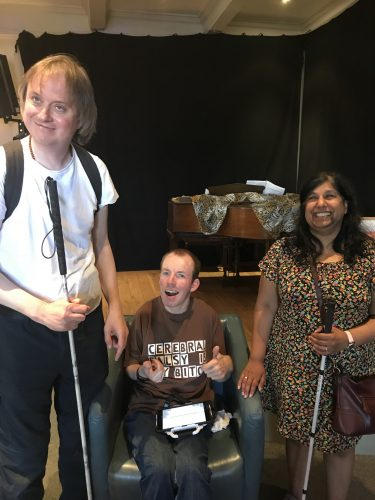 Photo of two visually impaired people smiling at the camera with performer Lee Ridley