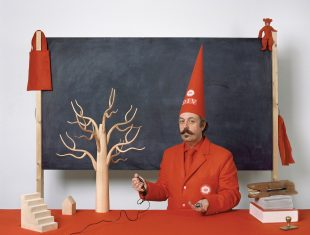 image of the artists wearing a red conical hat, standing in frot of a blackboard