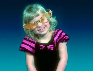 a small girl smiles at the camera wearing large tinted glasses