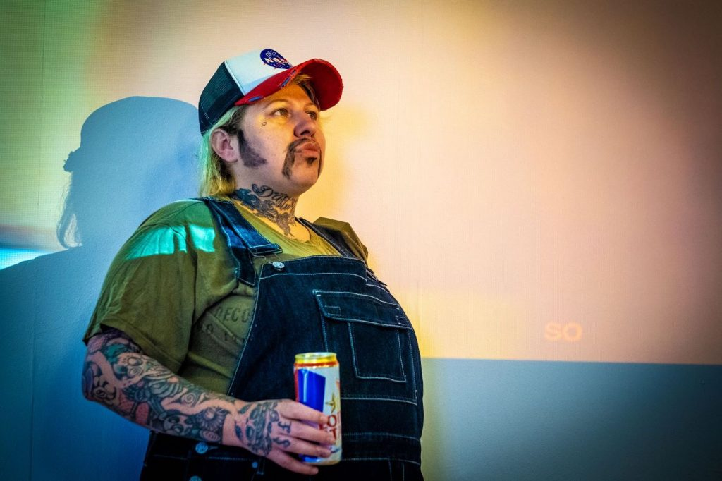 Performer dressed in denim overalls and a baseball cap and wearig a long moustache and sideburns, carries a can of beer