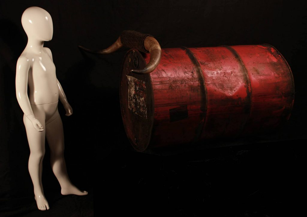a naked, plastic figure stands beside a large red barrel