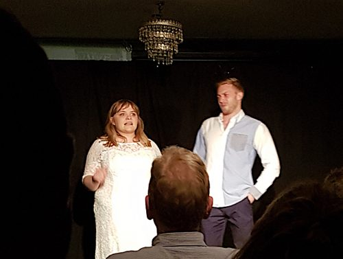 An actor and actress dressed in white against a dark stage