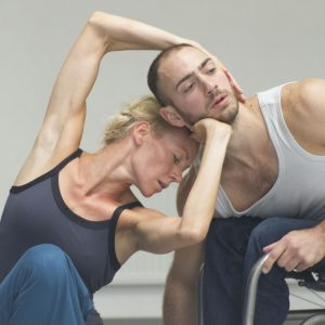 a female dancer poses with her hands around the face of a male dancer