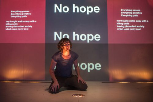 an actor sits on stage in subdued light against a wall with the words 'no hope' repeated several times