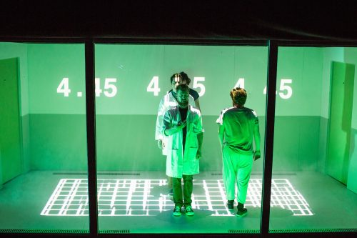 a group of actors pose behind a screen bathed in green light