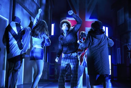 a group of actors dance in front of a union jack flag