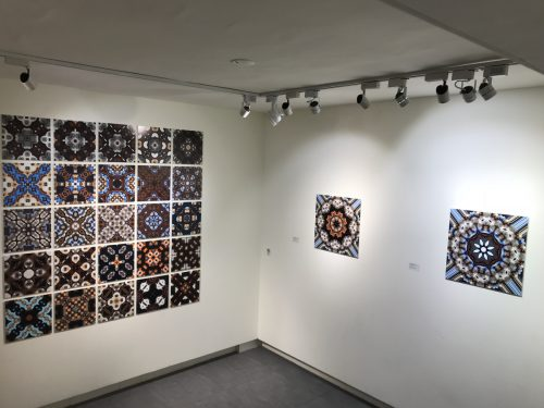 white gallery space with several brightly patterned artworks