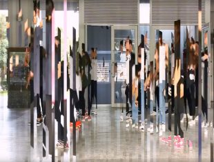 a number of people dance in a space, their image refracted through a digital process
