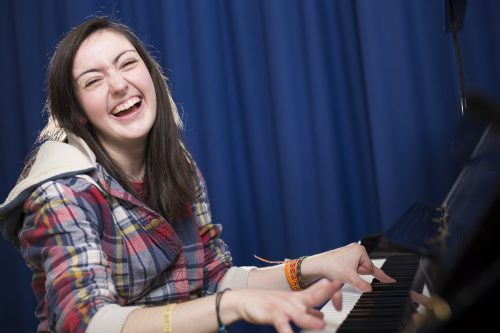 Performer sits a a piano, smiling at the camera