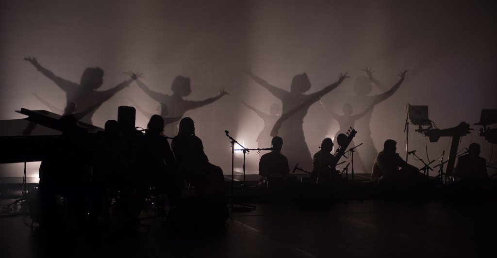 A dark sepia image showing the silhouettes of musicians and dancers performing on stage in a dramatic pose