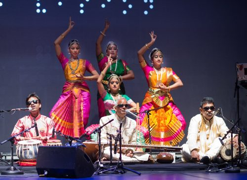 Three blind musicians, dressed in white sit on a stage with their instruments while four classical Indian dancers dressed in brightly coloured costumes stand, posing behind them