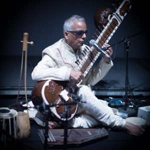 A blind musician dressed in white poses with his sitar