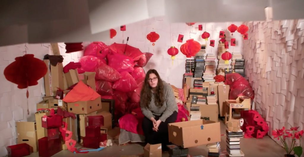 a young woman sits in a space filled with objects
