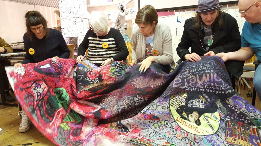 People holding colourful tapestry