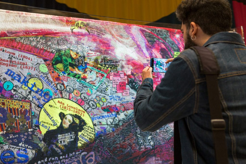 Man photographs tapestry with phone