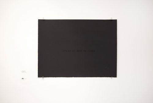 A black canvas sits against a white wall