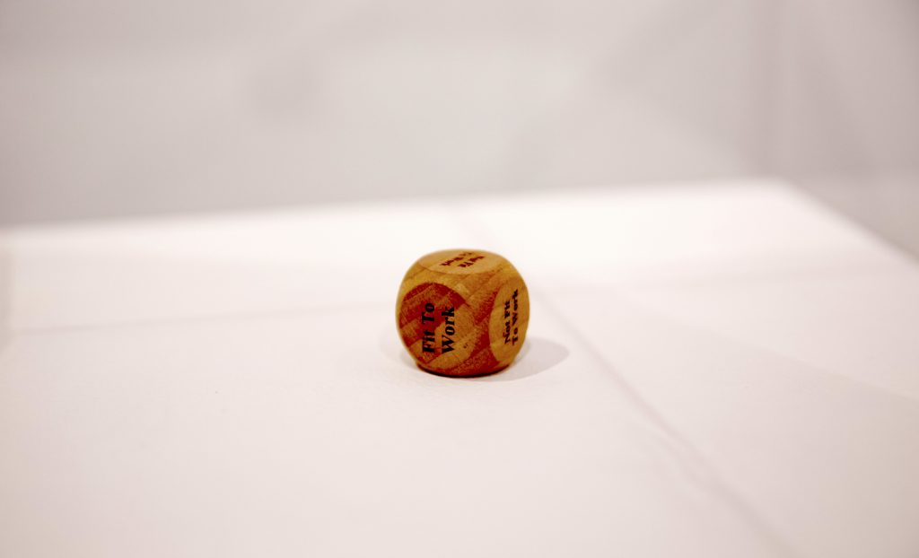 a six sided dice with the words 'fit for work' sits on a white background