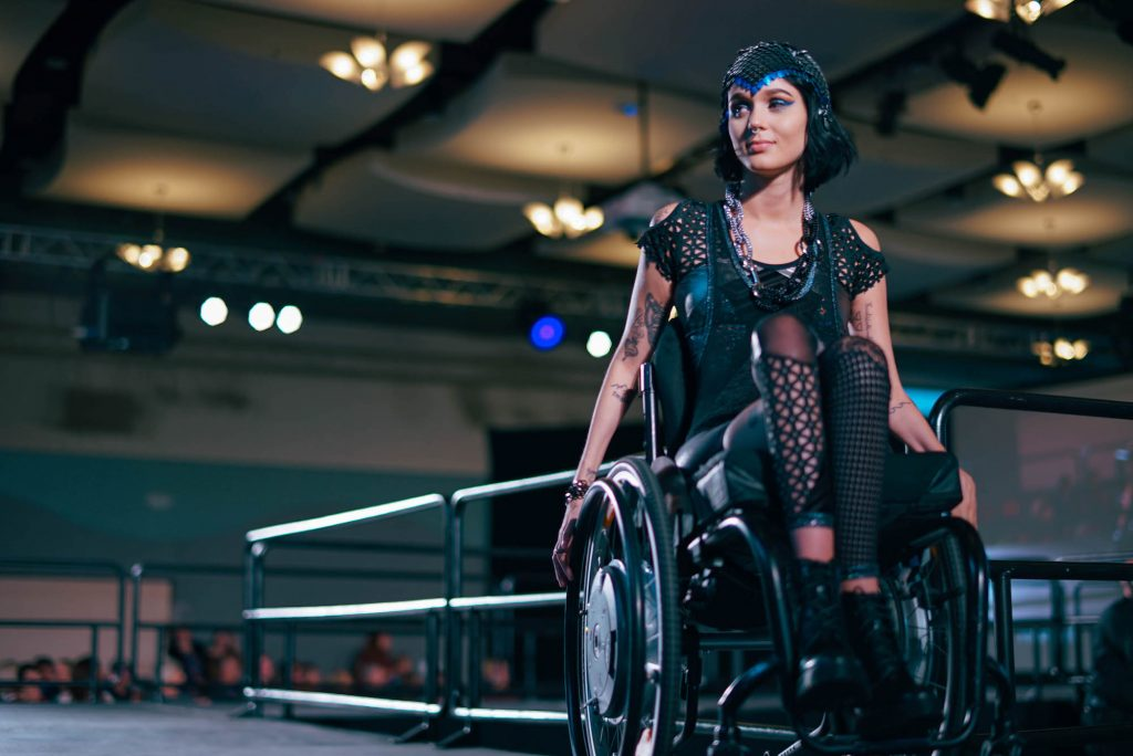 A young female wheelchair-user is dressed in a space age costume