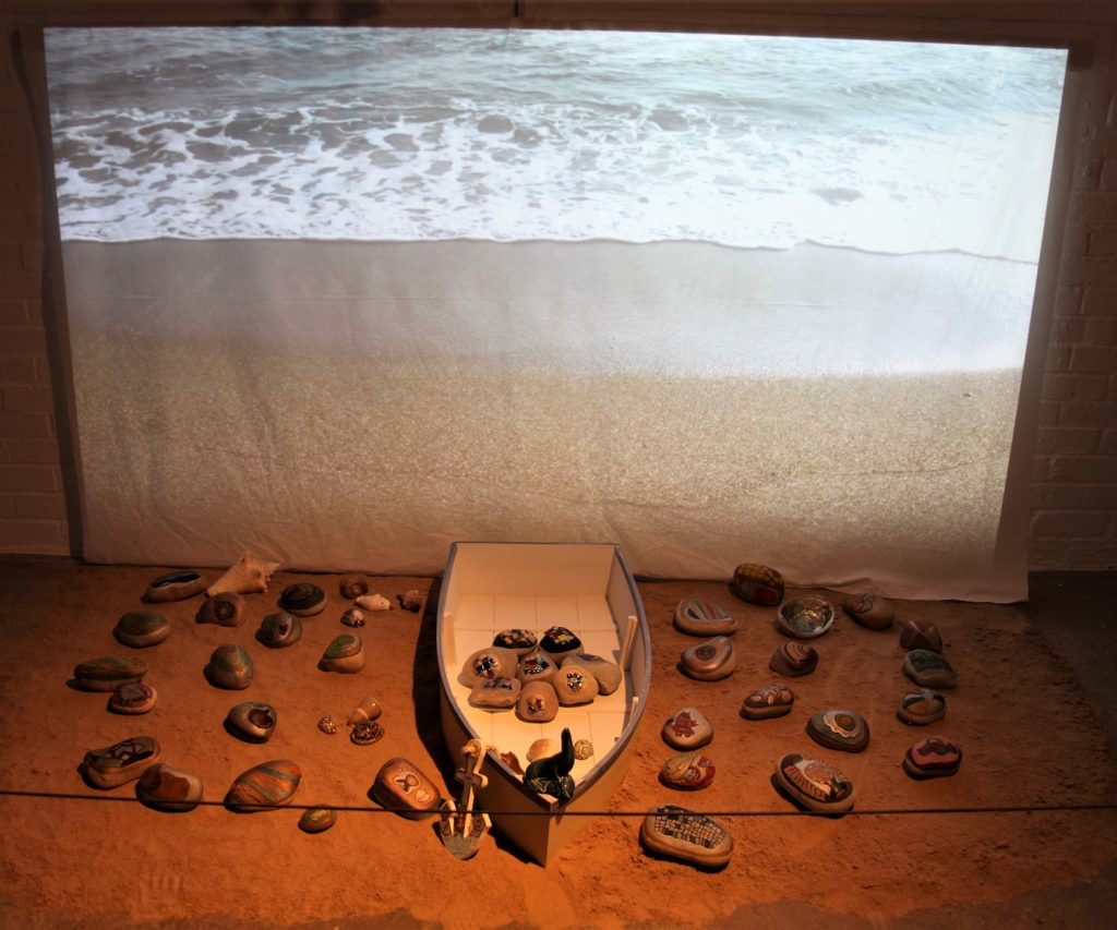 Image of an installation comprising of a wooden boat surrounded by painted pebbles against a backdrop of the sea