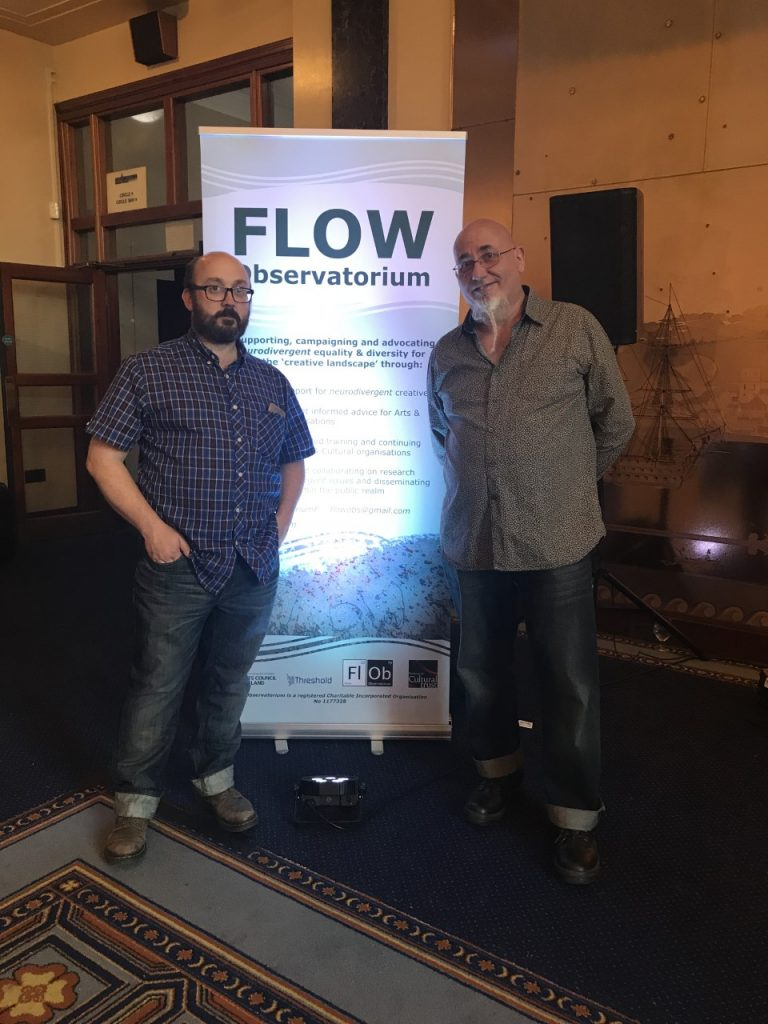 Two men stand deside a large FLOW banner