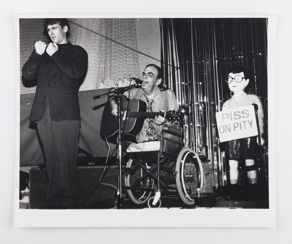black and white photo of disabled musician performing alongside charity sculpture Chip