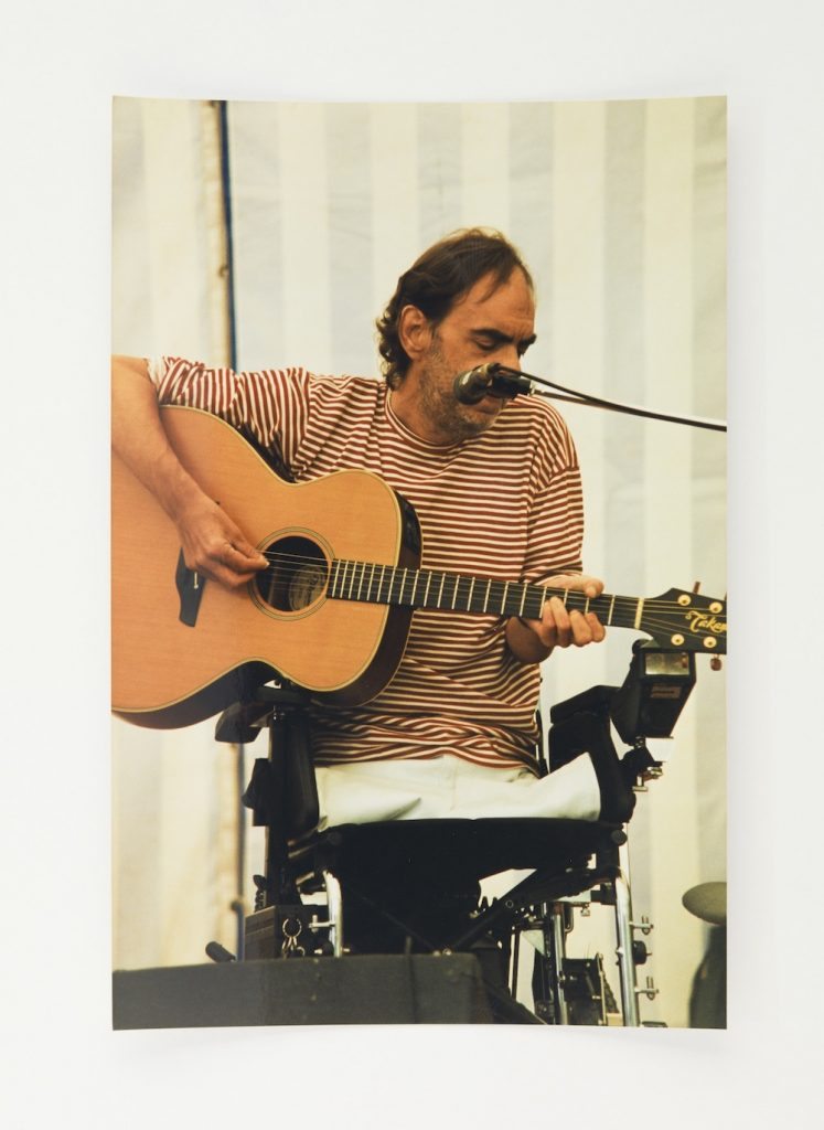 Photo of a man who has no legs playing guitar