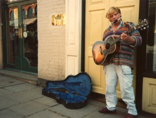 A young Alan Holdsworth performs as Johnny Crescendo busking on a street corner