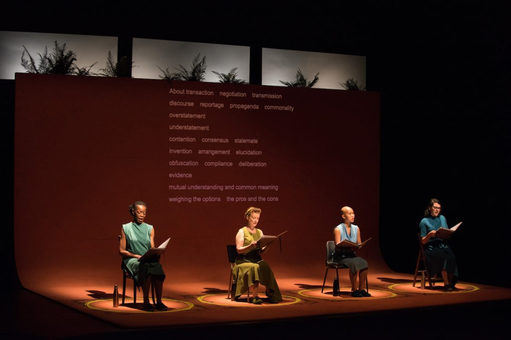 four women of different racial backgrounds sit in a row on chairs on a stage
