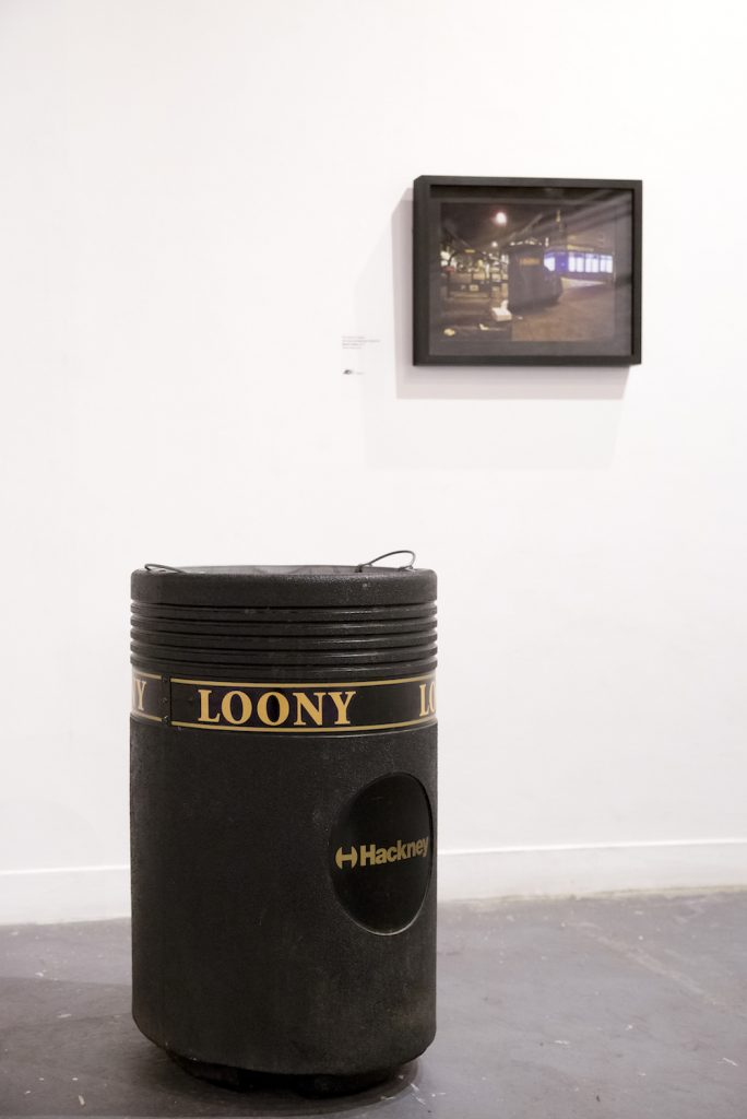a black bin with the word 'loony' on it, sits in the gallery