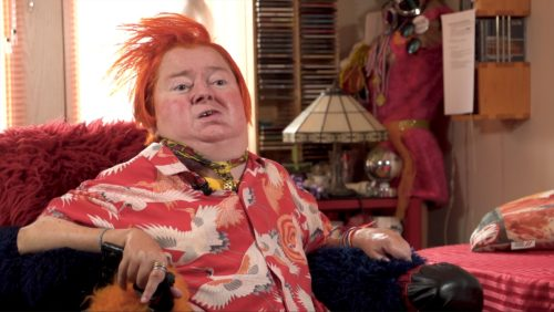 A woman with bright red hair sits in wheelchair wearing matching top