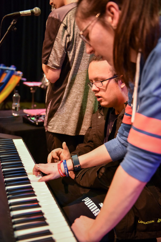 A young disabled woman shows a young man sitting at a keyboard where to place his fingers