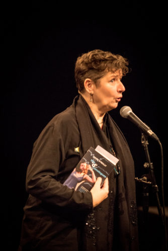 A female playwright is pictured standing at a mike with a copy of her publication under her arm