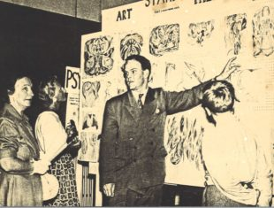 Sepia image of the psychiatrist showing a panel filled with artwork to an audience