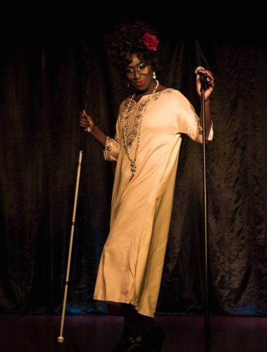 A performer of colour stands wearing a dress, holding two visual impairment sticks