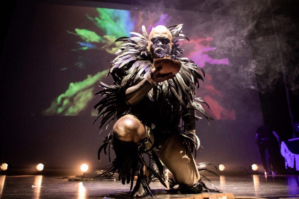 Lasana Shabazz crouching on stage