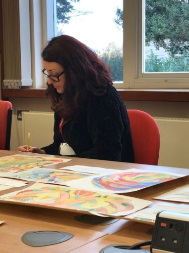 A young woman sits at a table with brightly coloured artwork