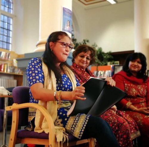 A young British Asian woman Kuli Kohli sits reading poetry in apublic library