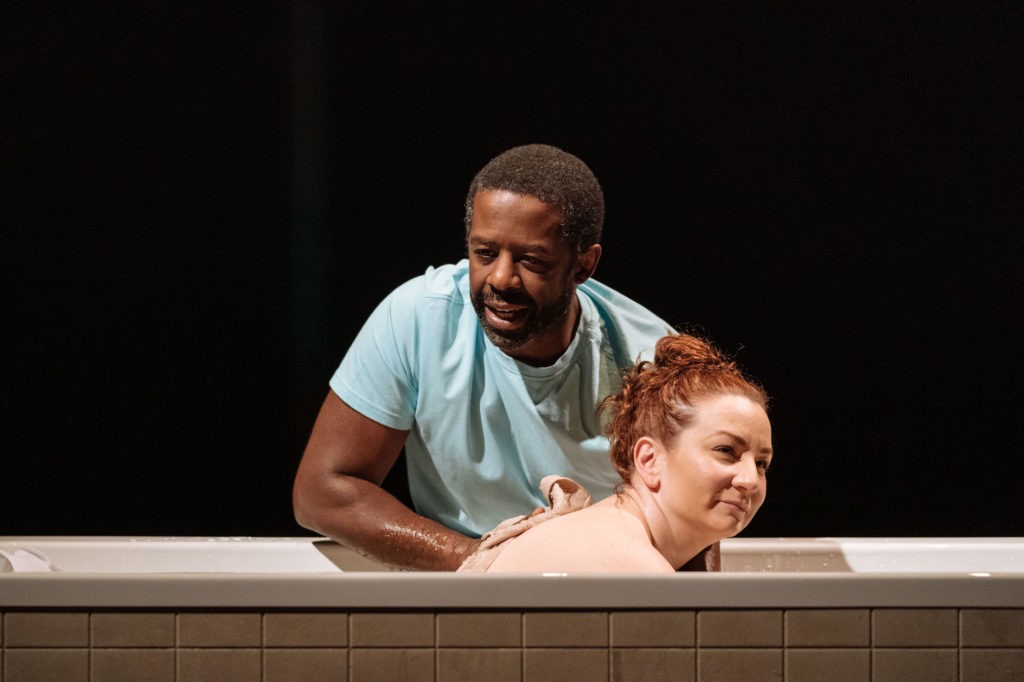 A black man leans over the edge of a bath, washing a white woman