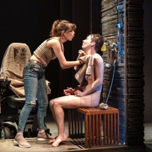 A white woman stands leaning over a a seated, naked white man who she is washing