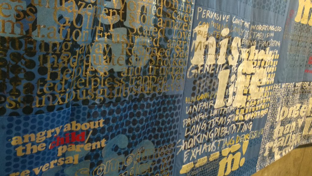 Blue textile work covered in differetn typefaces