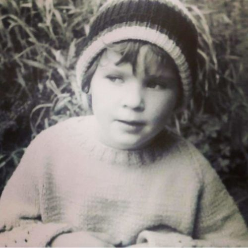 black and white photo of small child in woolly hat not looking at the camera