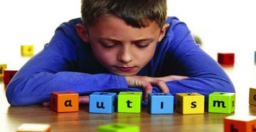 boy in bltue jumper looking at coloured blocks spelling out the word autism