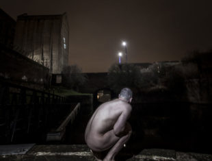 a naked man crouches in a dark landscape