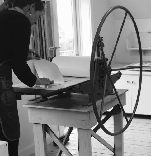 black and white photo of a woman at printing machine
