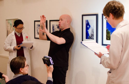 A photo shows four people in front of visual artworks hanging on a wall. One person lights the work with a hand-help lamp, to the right and left two people audio-describe the artworks. In the centre, a man interprets what they're saying for the tour audience.