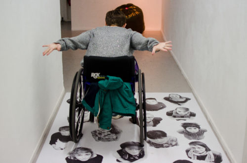 A wheelchair-user photographed from behind as they wheel over an artwork affixed to the floor. Their arms are held out behind them, as if wheeling with force or enjoyment. The artwork they traverse consists of life-sized black and white photos of many people.