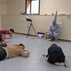 People sitting on floor in workshop